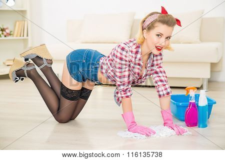 Young attractive girl is mopping the floor.