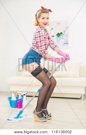 Young attractive girl is playing with mop.
