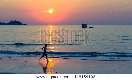 Silhouette of man running on coast line during amazing sunset.