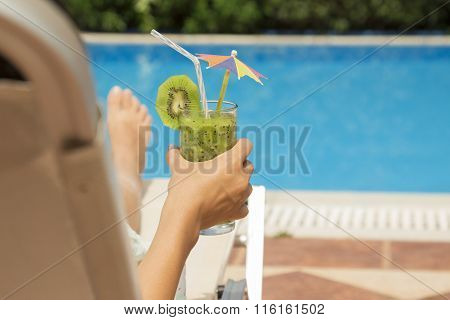 Female lying on sunbed and holding a glass of kiwi smoothie