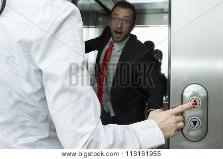 Businesswoman pressing elevator up button. Businessman confused trying to stop the elevator.