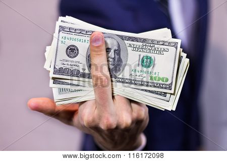 Stack of dollars and  rude gesture