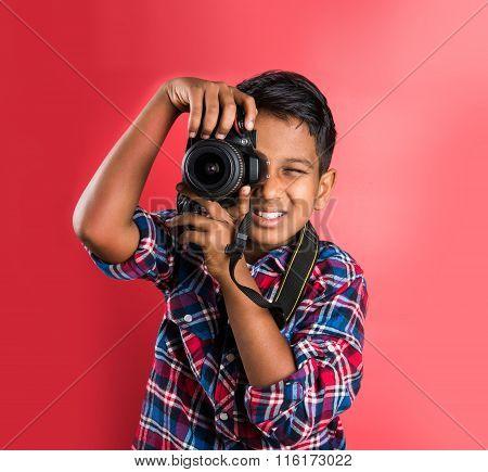 10 year old indian boy holding digital camera or DSLR camera, posing like a professional photographe