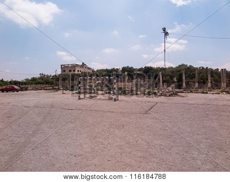 Football Field And Parking In Close Proximity To The Ruins Of Ancient Columns