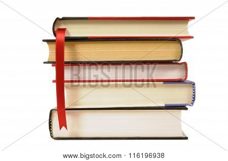 Small Stack Of Hardback Books With Bookmark Ribbon Isolated On White Background.