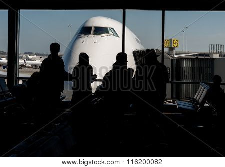 Silhouette Of Passengers Waiting For Their Flight