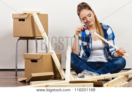 Woman moving into new apartment house assembling furniture using scredriver. Young girl arranging interior and unpacking boxes. DIY. poster
