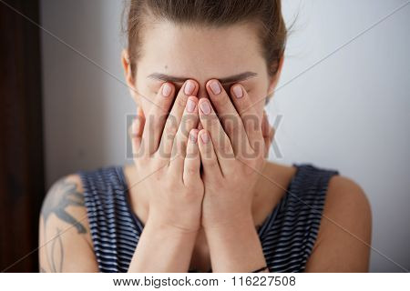 Frustrated stressed young woman. Headshot unhappy overwhelmed girl having headache bad day keeps hands on face out isolated on wall background. Negative emotion face expression feelings perception poster