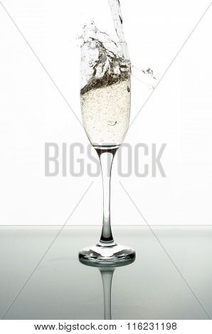 Pouring Champagne Into Glass On White Background