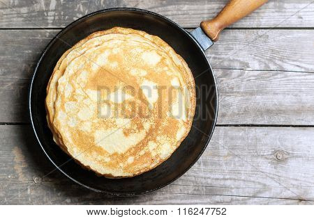 Stack of pancakes on a cast-iron frying pan. Top view poster