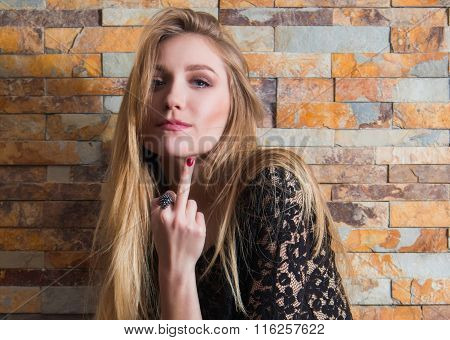 Portrait of beautiful young woman insulting with finger