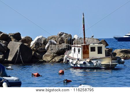 Small Boat Is Docked In A Harbor