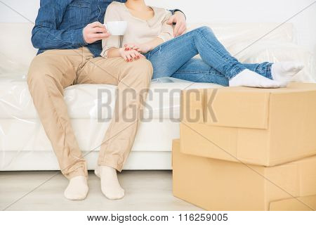 Cheerful couple resting on the sofa