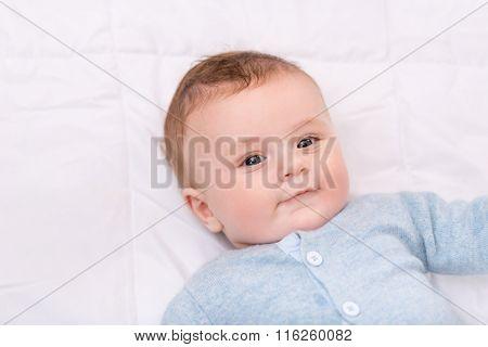 Cute infant boy lying in bed.