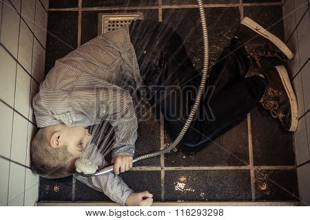 Boy Holding Shower Head Collapsed In The Rest Room