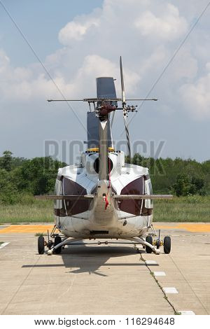 rear view of helicopter park on concrete helipad with green forest and blue sky background