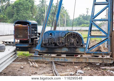 engines and transmission of old pile driver at construction site