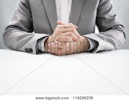 Businessman at desk in business job interview with hands clasped, attentive and listening in anticipation poster