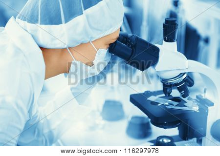 Young Woman Medical Researcher Looking Through Microscop Slide In The Life Science (forensics, Micro