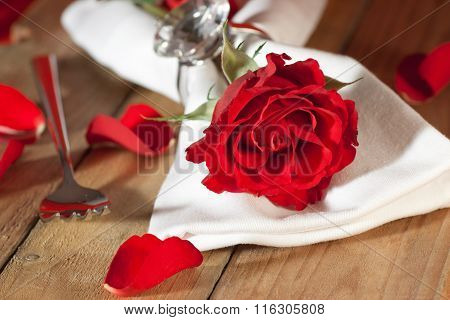 Place setting in silver with a red rose in country style