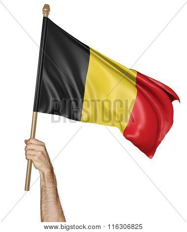 Hand proudly waving the national flag of Belgium