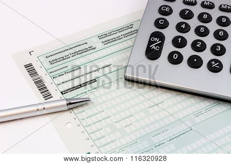 Form of income tax return with ball pen and pocket calculator in Germany