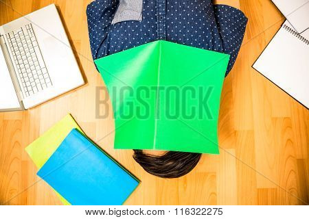 Hipster with book on face on hardwood floor in office