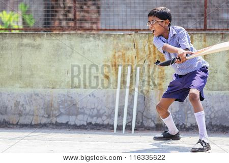 KOLKATA, INDIA - APRIL 14, 2013: Poor indian boy plays cricket after receiving his new glasses