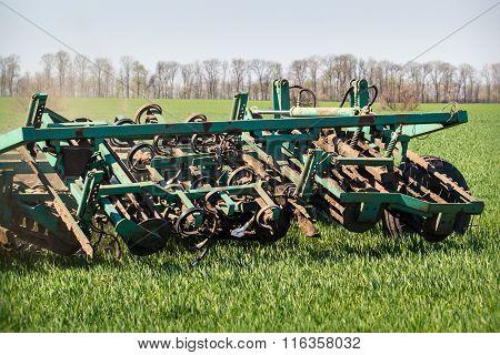 Closeup Weeding-machine Behind Tractor On Green Wheat Field