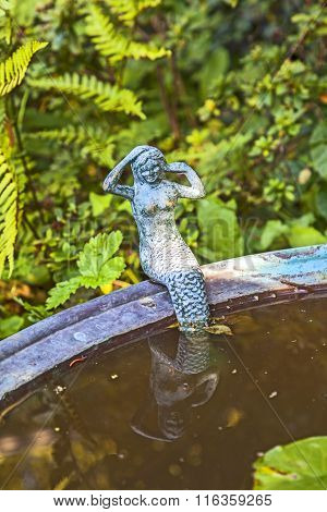 Little Murmaid Sitting On The Edge Of A Metal Basin And Looking Magical