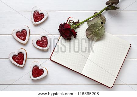 Heart shaped cookies with empty notebook frame and red rose gift composition for Valentines Day
