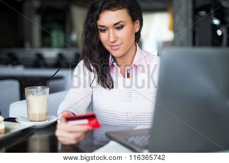 Woman doing online shopping at cafe, holding credit card typing numbers on laptop computer.