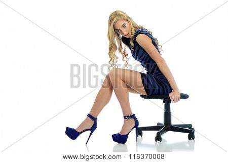 Young blond woman wearing a blue dress and high heels isolated on a white background