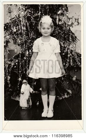 USSR - CIRCA 1980s: Vintage photo shows a small girl (about 7 years old) in front of Christmas tree.
