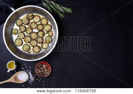 Vegetarian dish, zucchini and rosemary, over dark wooden background. Flat lay, copy space.