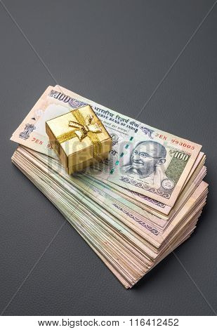 A tiny gift box placed on a hip of hundred rupee notes. Cash rewards concept.
