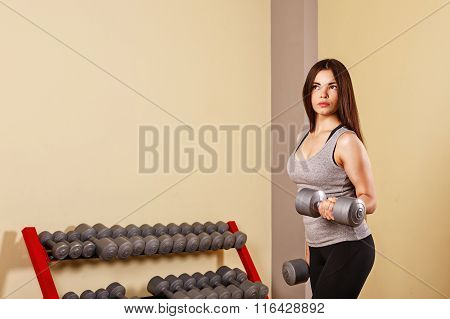 Girl Athlete Trains Biceps With Dumbbells.