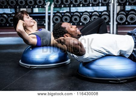 Fit couple doing bosu ball exercises at gym
