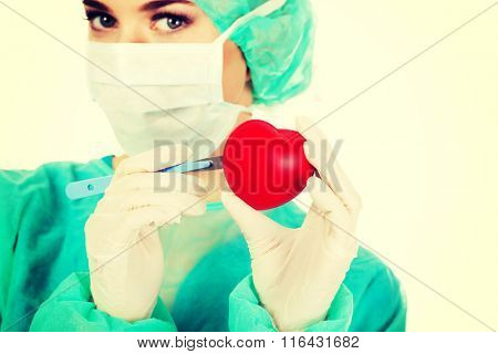 Young female cardiologist surgeron holding heart and scalpel