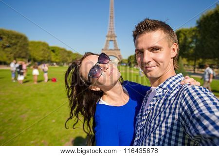 Young happy family taking self portrait in Paris background the Eiffel Tower. Young adults holding s