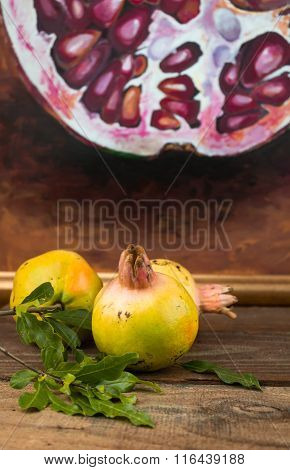 Whole Unripe Pomegranates With A Blurred Painting Background On Rustic Table