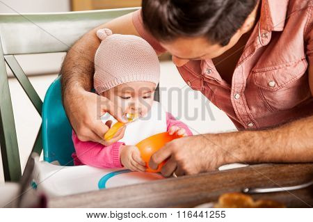 Father Feeding His Baby Girl At Home
