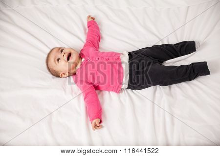 Happy Baby Girl Lying On A Bed