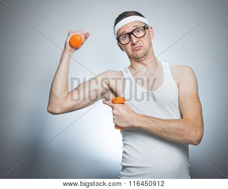 Nerd man showing his small biceps over gray background. Funny sport weak male ready for exercising - training poster
