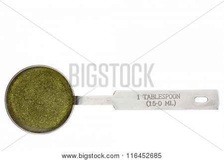 wheatgrass powder in a metal measuring tablespoon isolated on white