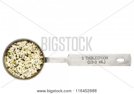 hemp seed hearts in a metal measuring tablespoon isolated on white
