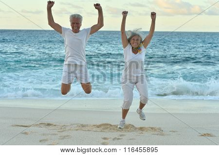 Senior couple  jumping on  seashore