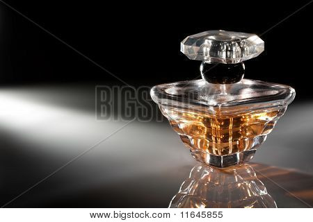 Bottle of perfume on dark background