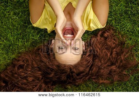 Portrait of a beautiful readhead woman lying on the grass