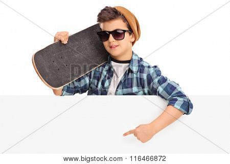 Cool kid holding a skateboard and pointing on a blank panel with his hand isolated on white background